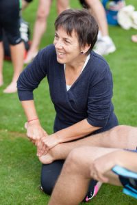 A registered osteopath manipulating a patient's foot at the end of a race
