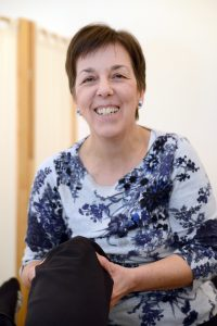 Carol Plumridge facing treating a knee, asking a question